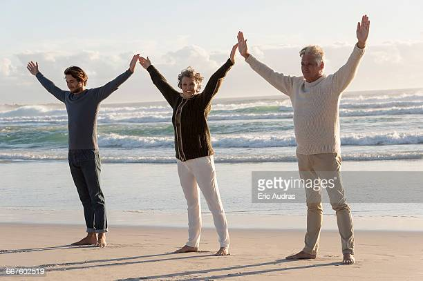 Happy family practicing yoga on the beach