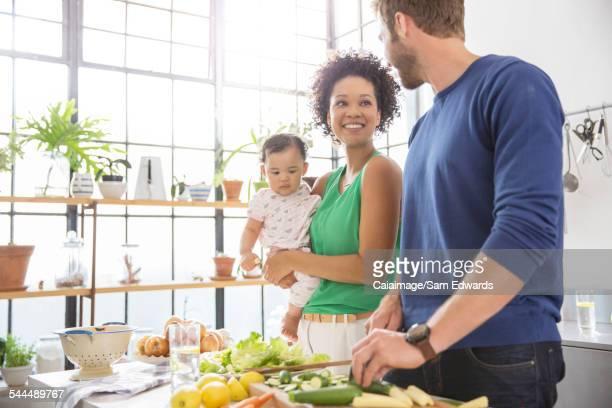 Happy family preparing meal in domestic kitchen