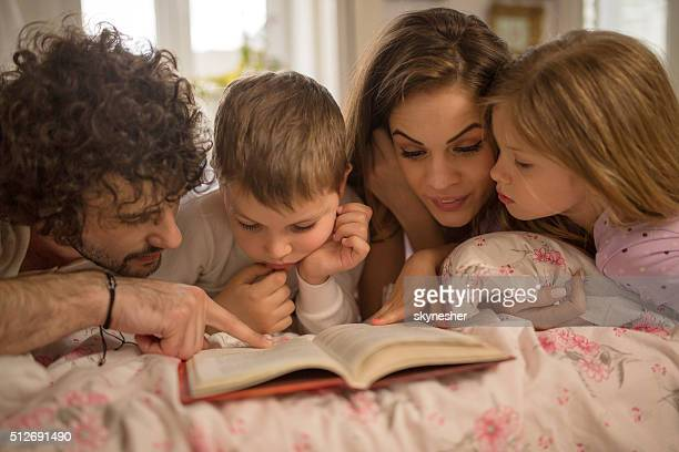 Happy family reading a story together in bed.