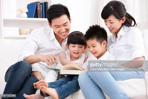Happy family reading book in sofa