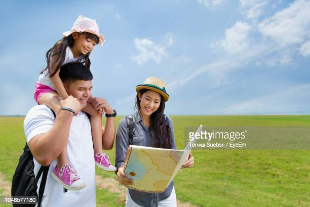 happy family reading map while standing on field against sky - torwai stock pictures, royalty-free photos & images