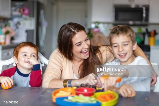 幸せな家族赤毛と金髪男の子と母アクティブとコンテンツでホーム - 中流階級 ストックフォトと画像