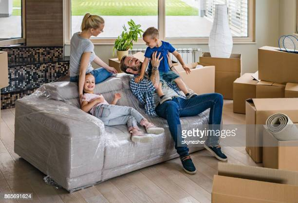 Happy family relaxing from unpacking their belongings and having fun in their new home.