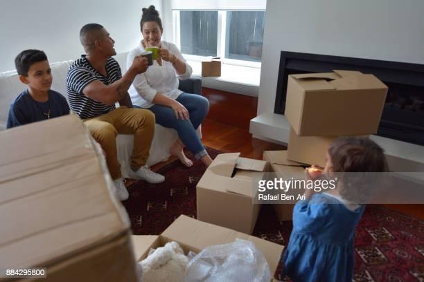 happy family relaxing in their new home - rafael ben ari stock-fotos und bilder