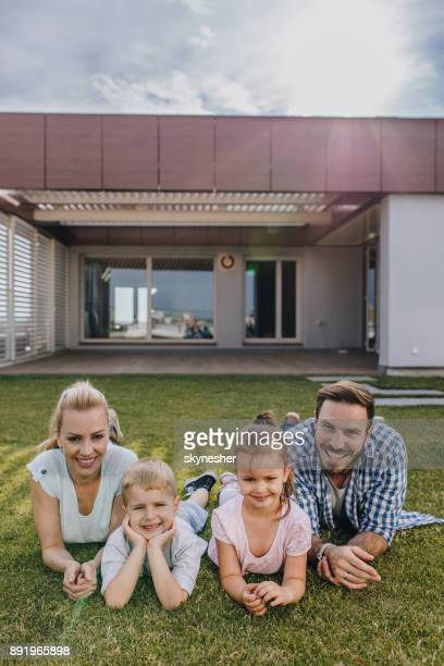 happy family relaxing on grass in front of their penthouse. - penthouse girl stock photos and pictures