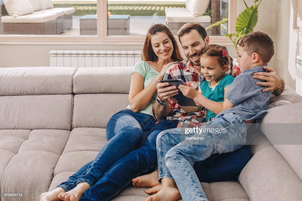 Happy Family Relaxing On Sofa In The Living Room And Using Digital Tablet.  : Stock