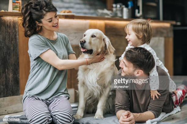 Happy family relaxing with their dog at home.
