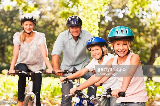 Happy family riding bicycle at park