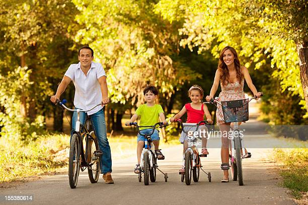Happy Family Riding Bicycles Outdoors.