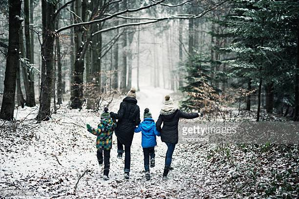 happy family running in beautiful winter forest - winter weather stock photos and pictures