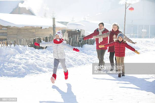 Happy family running in the snow