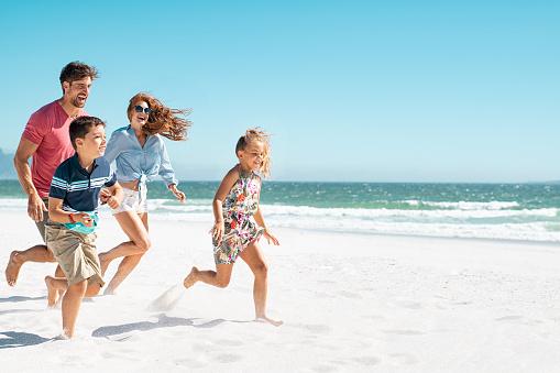 Happy family running on beach 1137373430