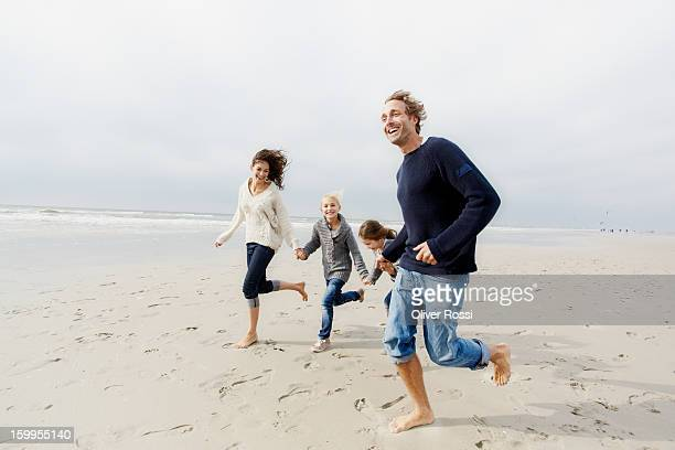 happy family running on the beach - barefoot stock pictures, royalty-free photos & images