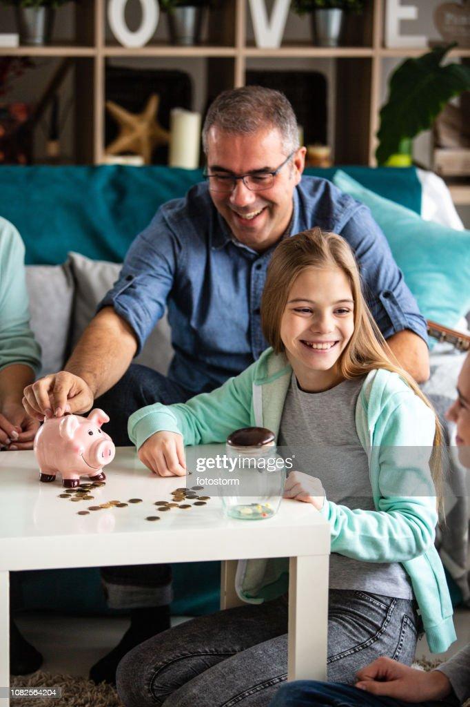 Happy family saving money : Stock Photo