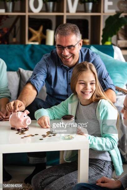 happy family saving money - 40 44 jaar stock pictures, royalty-free photos & images