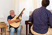 happy family senior father playing guitar