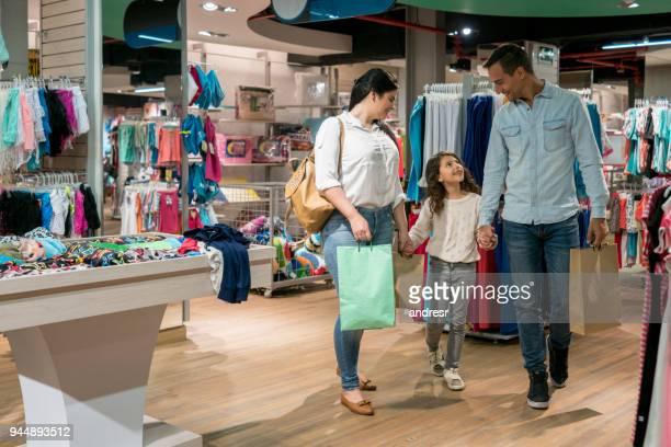 happy family shopping for clothes at a store - spending money stock pictures, royalty-free photos & images