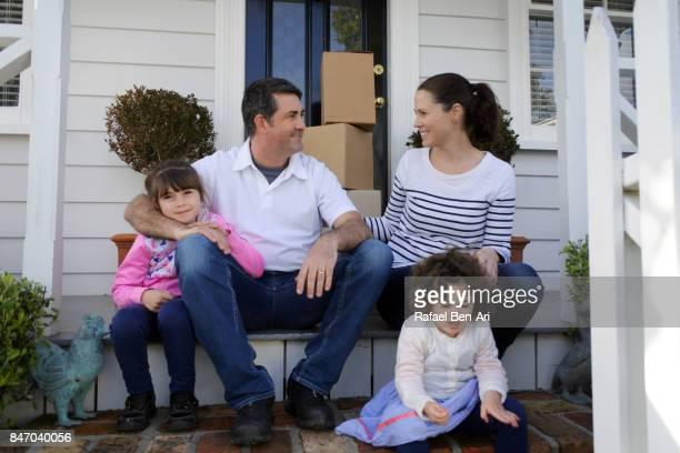 happy family sits outside their new home - rafael ben ari photos et images de collection