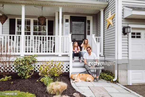 gelukkige familie zitten voor thuis - voor of achtertuin stockfoto's en -beelden