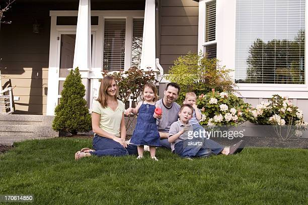 Happy family sitting in front of their home on the grass