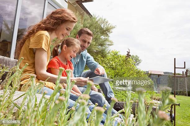 Happy family sitting in garden using tablet