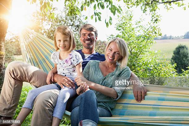 Happy family sitting in hammock