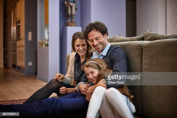 happy family sitting in living room leaning against couch - black women wearing pantyhose stock pictures, royalty-free photos & images