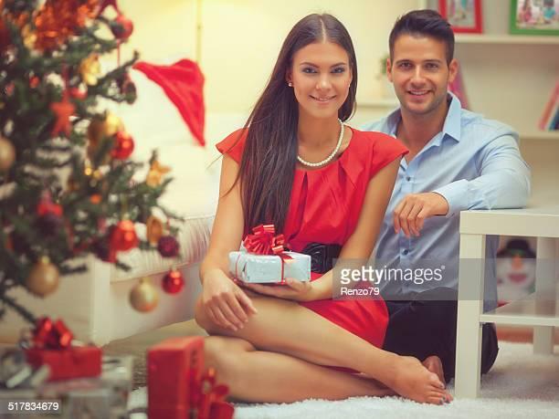 Feliz Familia sentada cerca de un árbol navideñas