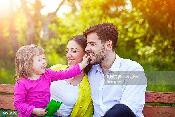 Happy Family Sitting on Bench in Woods