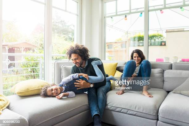 happy family sitting on couch, father tickling his laughing daughter - famiglia con figlio unico foto e immagini stock