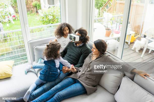 Happy family sitting on couch, father wearing VR goggles