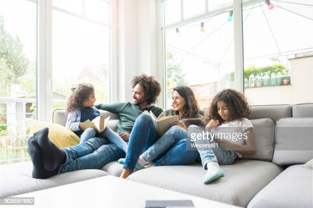 happy family sitting on couch, reading books - mixed race person stock pictures, royalty-free photos & images