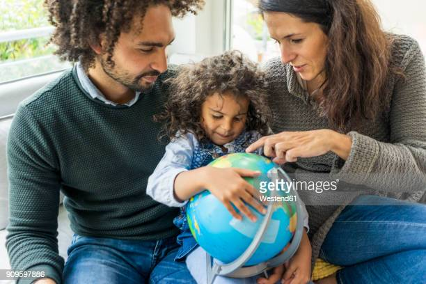 happy family sitting on couch with globe, daughter learning geography - origins stock pictures, royalty-free photos & images