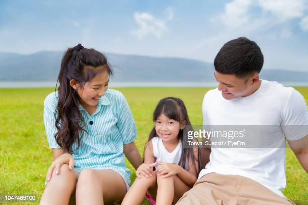happy family sitting on grassy field against sky - torwai stock pictures, royalty-free photos & images