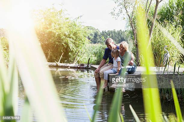 Happy family sitting on jetty at a lake