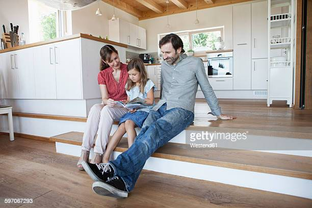 Happy family sitting on kitchen steps, parents reading book with daughter