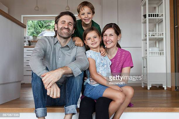 Happy family sitting on kitchen steps