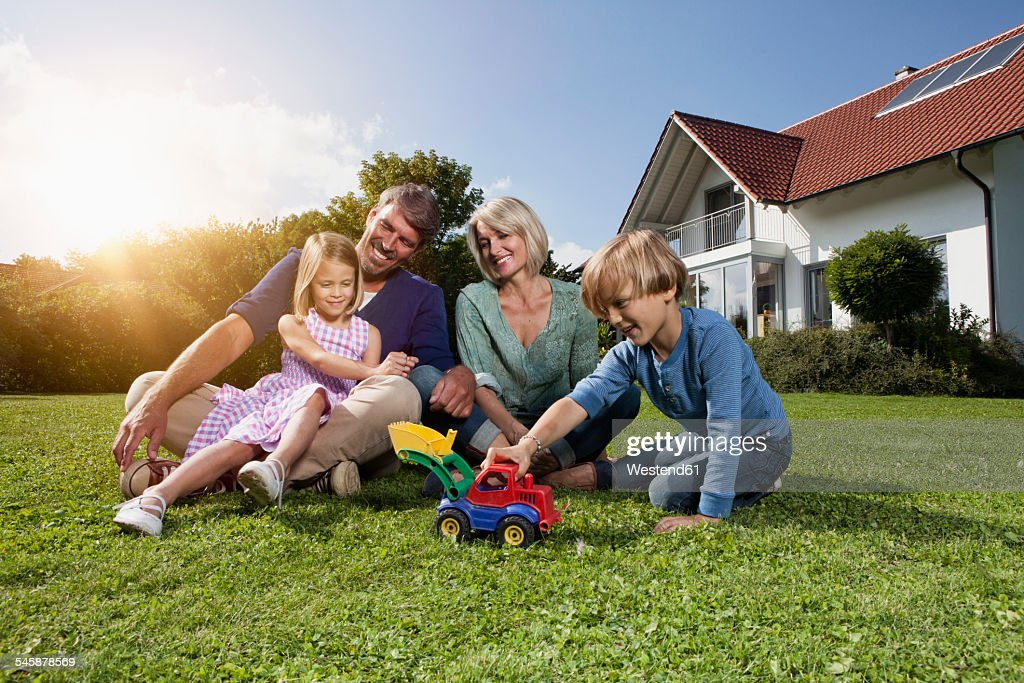 Happy family sitting on lawn in garden : Stock-Foto