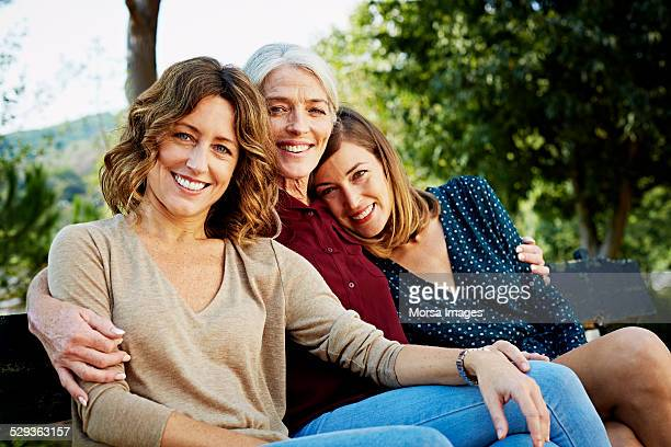 happy family sitting on park bench - two generation family stock pictures, royalty-free photos & images