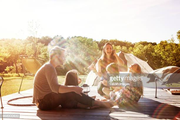happy family sitting on porch - camping stock-fotos und bilder