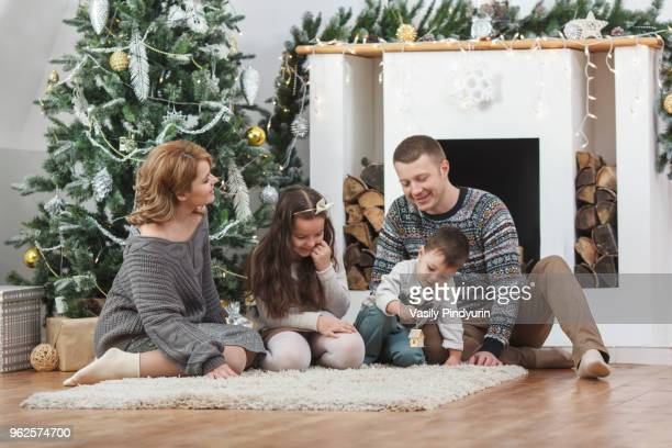 Happy family sitting on rug by Christmas tree at home