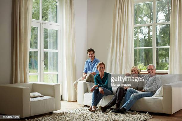 Happy family sitting on sofa in country house