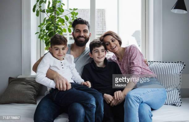 happy family sitting on sofa in living room at home - cuatro personas fotografías e imágenes de stock