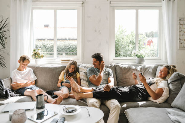 happy family sitting on sofa in living room - parents and children at home stock pictures, royalty-free photos & images