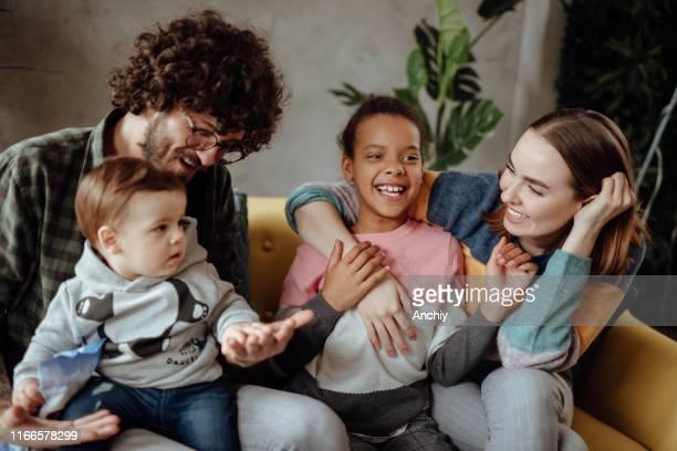 familia feliz sentada en el sofá - adopción fotografías e imágenes de stock