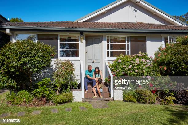 Happy family sitting outside house in summer
