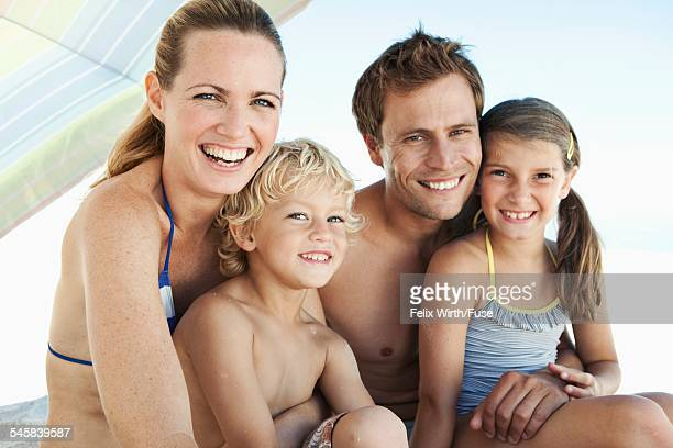 Happy family sitting with son (5-6) and daughter (10-12) on beach