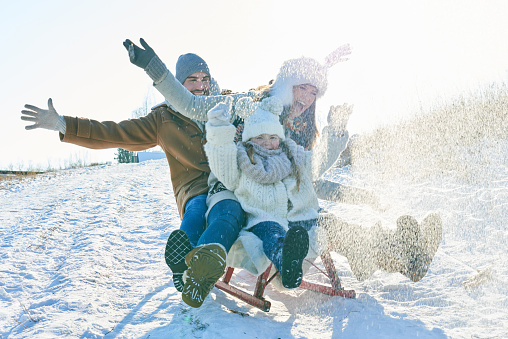 Happy Family Sledding On Snow Covered Field Against Sky - gettyimageskorea
