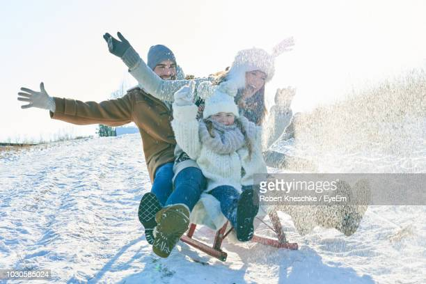 happy family sledding on snow covered field against sky - winter stock pictures, royalty-free photos & images