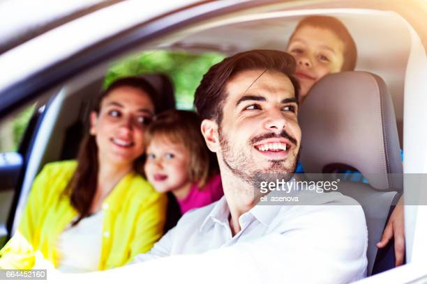 happy family smiling at the camera in car - family driving stock photos and pictures